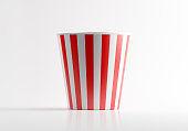 Red and white striped popcorn bucket. Popcorn bucket is empty and made of paper. Vertically stripped. Lit from the right upper corner of composition and casting shadows on a white reflective surface.