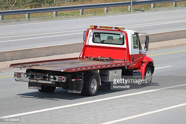 Red and white tilt bed tow truck on an empty highway