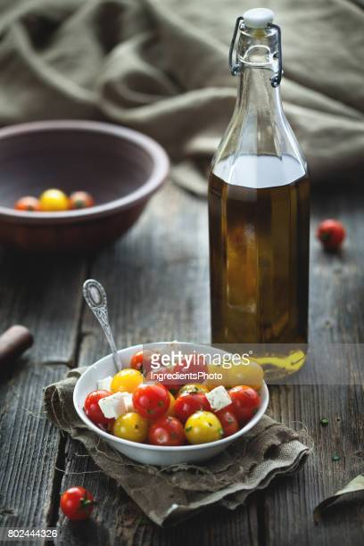 Red and yellow cherry tomatoes in bowl on wooden table.