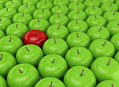 Red apple selected on the background of green apples