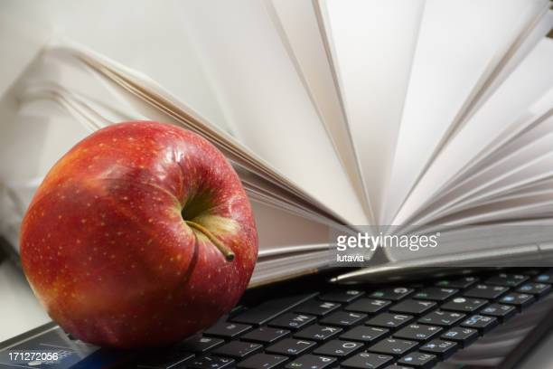 red apple on a computer and notebook with pen