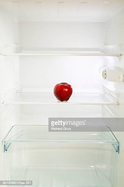 Red apple on fridge shelf