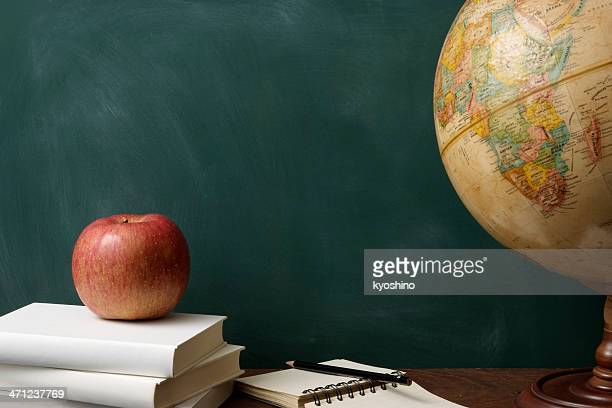 Red apple on stacked blank books with globe against blackboard
