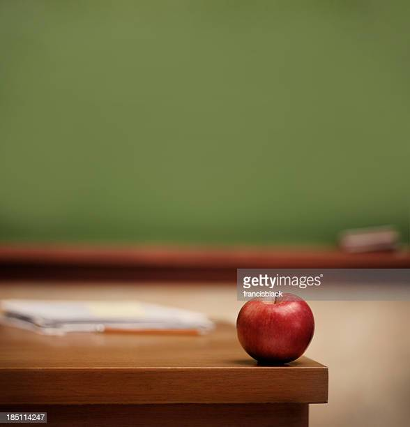 Red apple on teacher's desk.