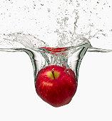 Red apple splashing in water