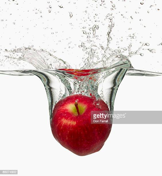 Red apple splashing in water