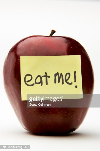 Red apple with adhesive note reading Eat Me : Stock Photo