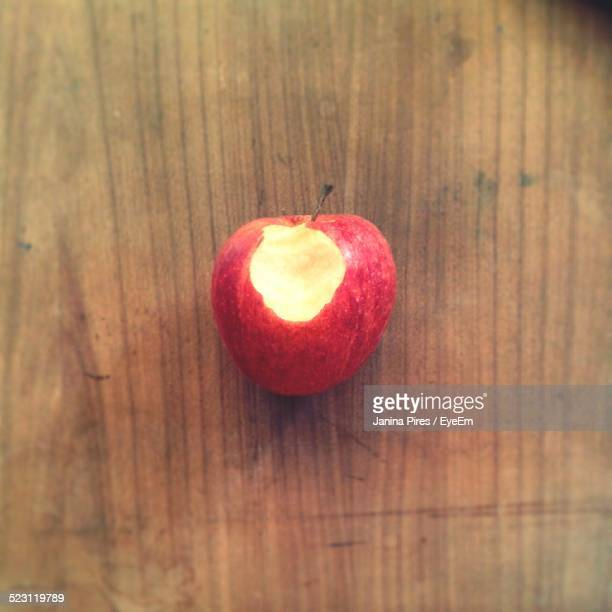 Red Apple With Bite On Wooden Table