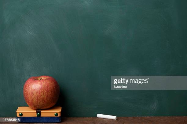 Red apple with eraser and chalk in front of blackboard