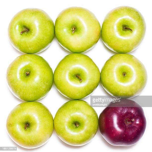 Pomme rouge dans des pommes vertes