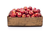 Front view of a wooden crate filled with fresh organic red apples sitting on white background. Predominant color is brown and red. DSRL studio photo taken with Canon EOS 5D Mk II and Canon EF 24-105mm