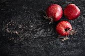 Red apples on a dark wooden surface.