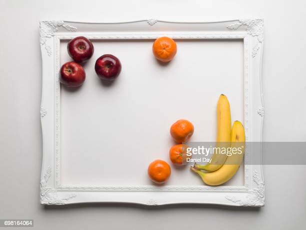 Red apples, tangerine and banana's colourfully displayed within a white frame on a white background