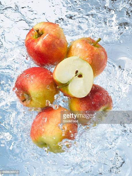 Red apples, whole & halved, dropping into water