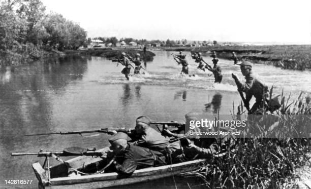 Red Army soldiers crounching in their boat cover the advance of their scouts as a reconnaissance party crosses a river in the Ukraine Donets Russia...