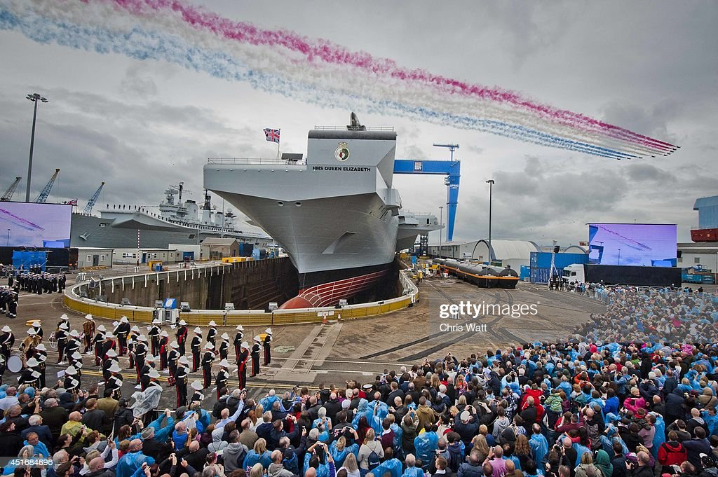 Red Arrows mark the naming of Royal Navy's new aircraft carrier HMS Queen Elizabeth by Queen Elizabeth II on July 4, 2014 in Rosyth, Scotland. HMS Queen Elizabeth is the largest warship ever built in the UK weighing 65,000-tonnes, six shipyards around the UK have been involved in building various parts of the carrier. The ship is capable of carrying up to forty aircraft, is scheduled to be launched later this summer, and to commission in early 2017, with full operational capability from 2020.