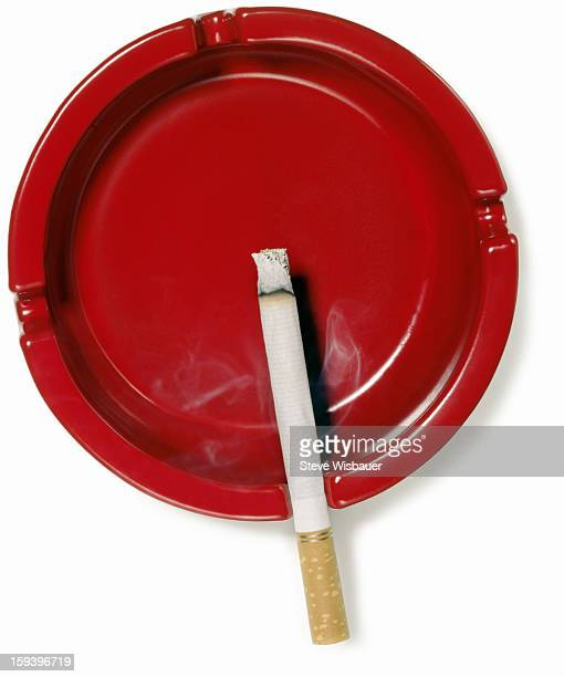 A red ashtray with a burning cigarette