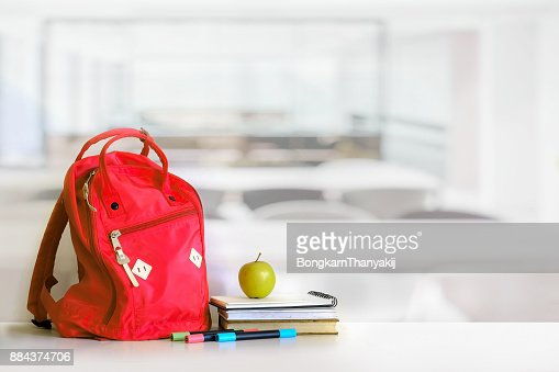Red backpack and books school supplies in classroom. : Foto de stock