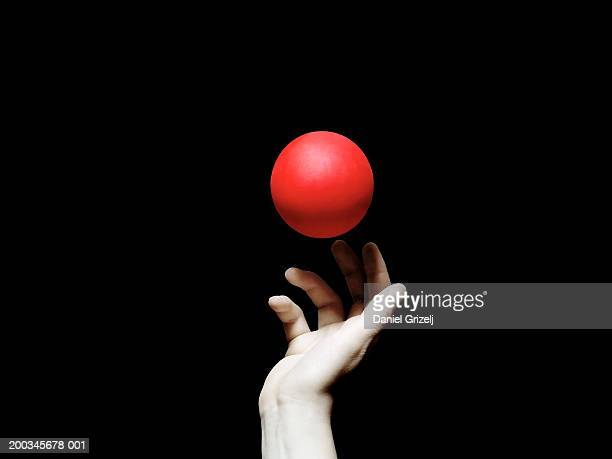 Red ball above woman's hand, close-up