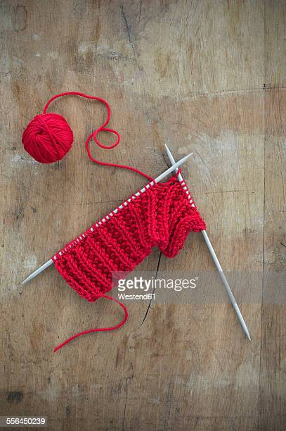 Red ball of wool and knitting on wood