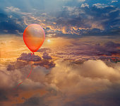 Red balloon floating in cloudy sky