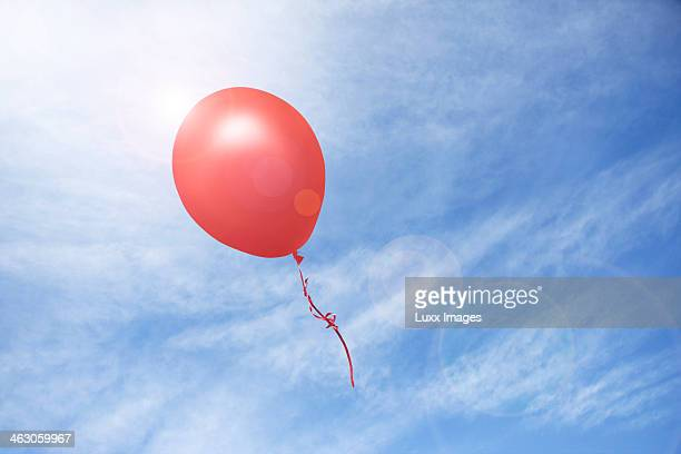 Red balloon floating into the distance