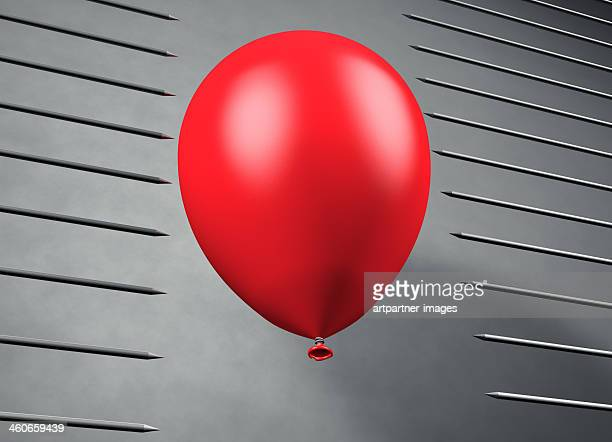 Red balloon floats between pointed steel nails