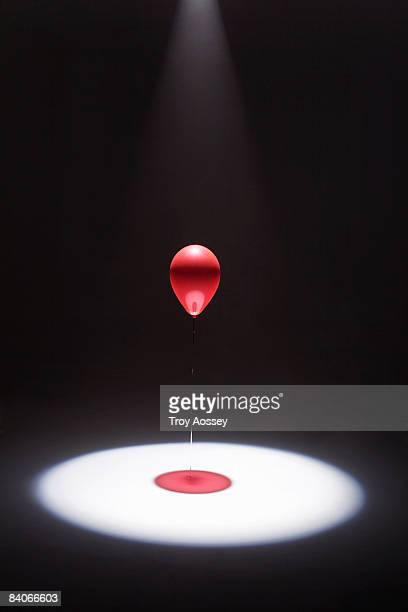 red balloon in shaft of white light