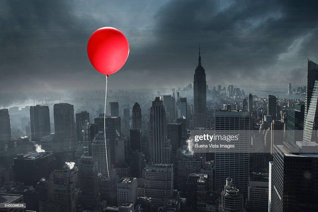 Red balloon over a gray city