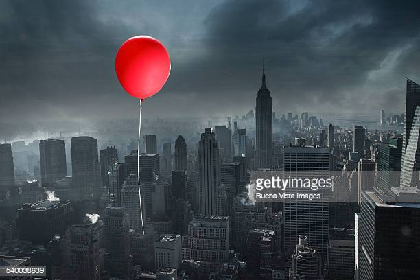 Red balloon over a gray city