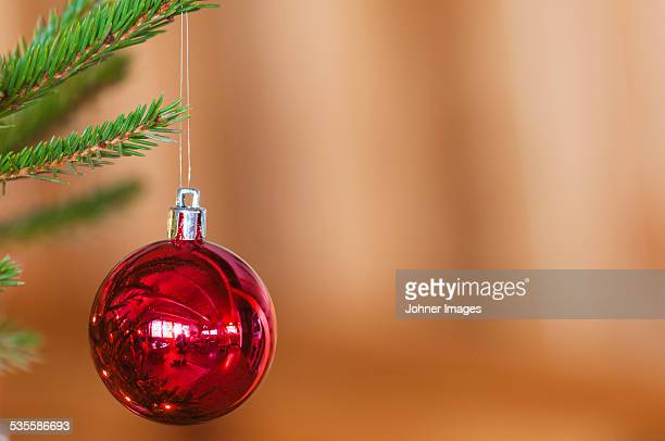 Red bauble hanging on Christmas tree, close-up