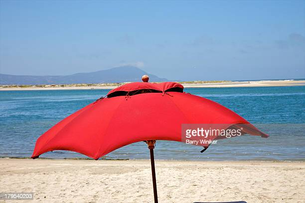 Red beach umbrella atop blue waters and white sand