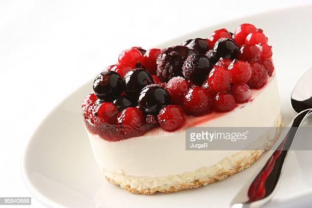 Bayas rojas postre de Cheesecake en una placa sobre fondo blanco