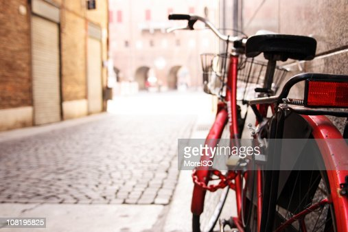 Red Bicycle Leaning Against Wall on Italian Street : Stock Photo