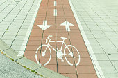 Red bike lane on sidewalk with painted white bicycle and arrow signs. Bicycle lane sign.