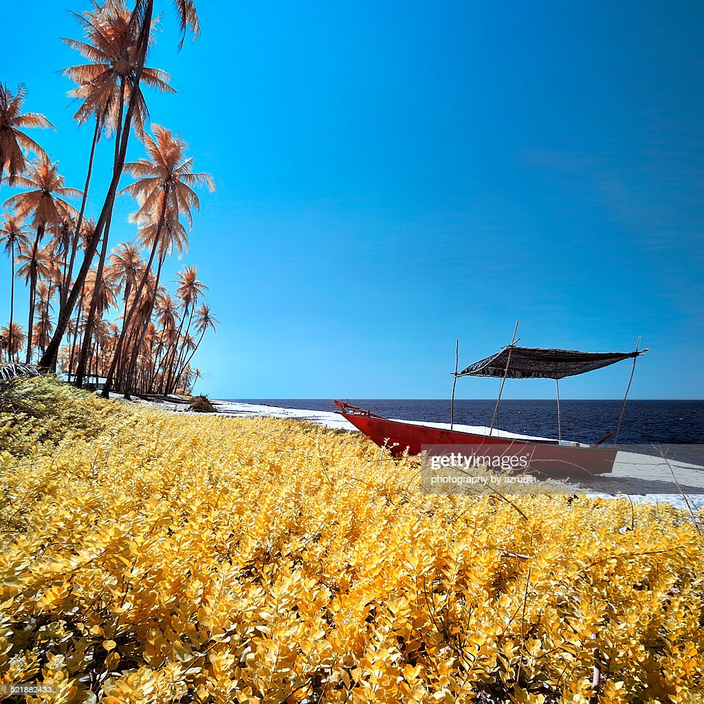 Red boat at white sand beach on the bright day