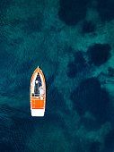Red boat in deep blue water. Aerial view from drone