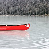Red Boat Moored On Lake Against Trees