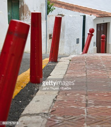Red Bollards On Street Against Building