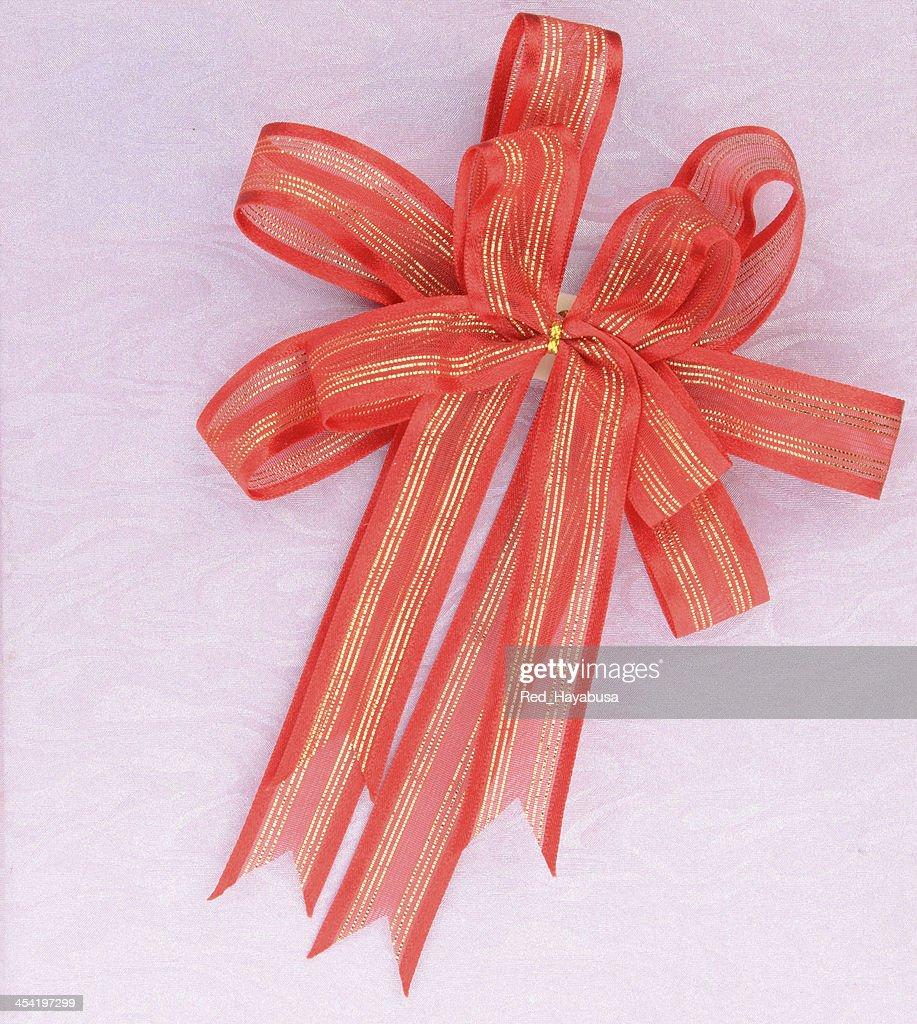 Laço vermelho em Fundo rosa : Foto de stock
