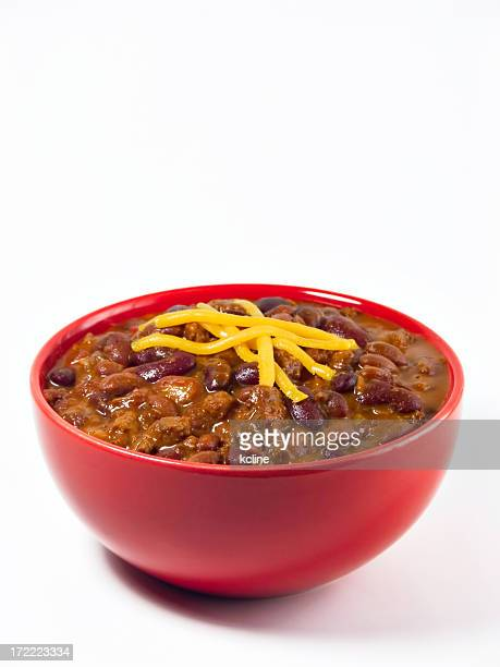 A red bowl full of chili on a white background