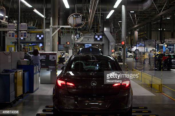 Red brake lights illuminate the trunk of an Opel Astra automobile as it near the end of the production line at General Motors Co's Adam Opel AG...