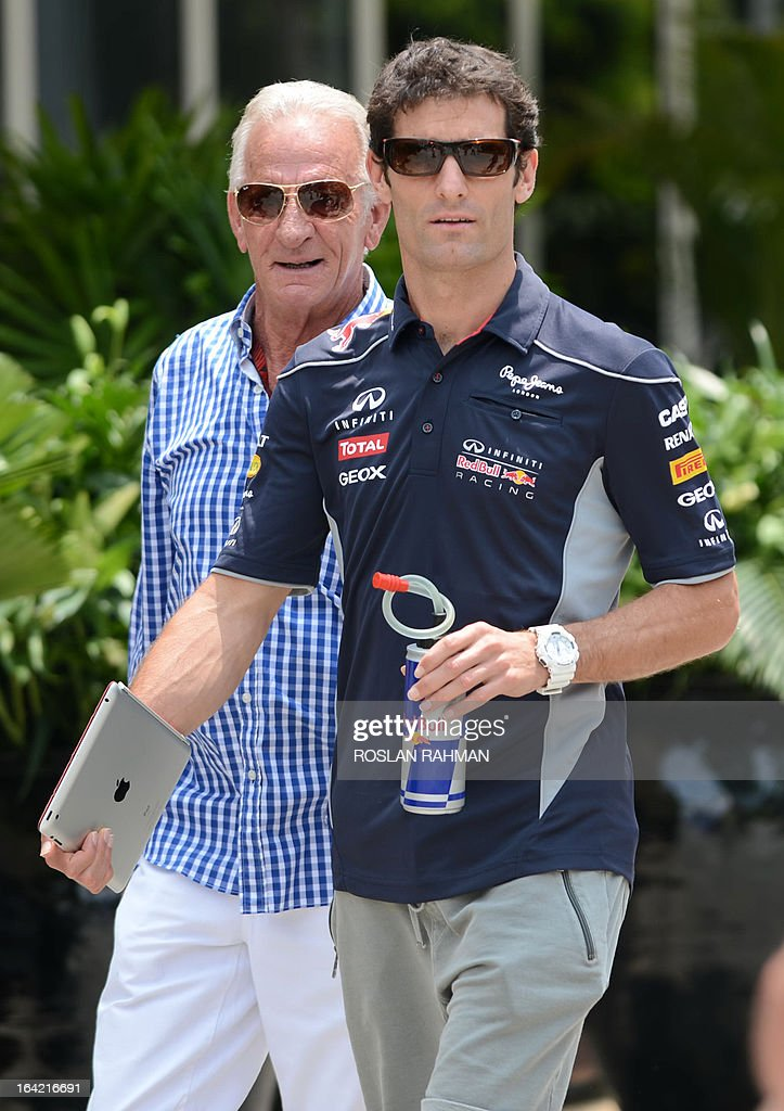 Red Bull driver Mark Webber of Australia (R) walks along the paddock ahead of the Formula One Malaysian Grand Prix at Sepang on March 21, 2013. The Malaysian Grand Prix will take place on March 24.