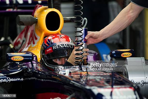 Red Bull driver Sebastian Vettel of Germany gives a canned drink back to his mechanic as he waits for his mechanics to adjust his car during a pit...