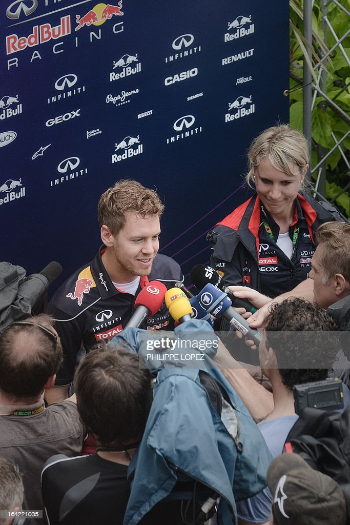 Red Bull driver Sebastian Vettel of Germany is interviewed by TV crews in the paddock of the Formula One Malaysian Grand Prix in Sepang on March 21, 2013. The Malaysian Grand Prix takes place on March 24. AFP PHOTO / Philippe Lopez