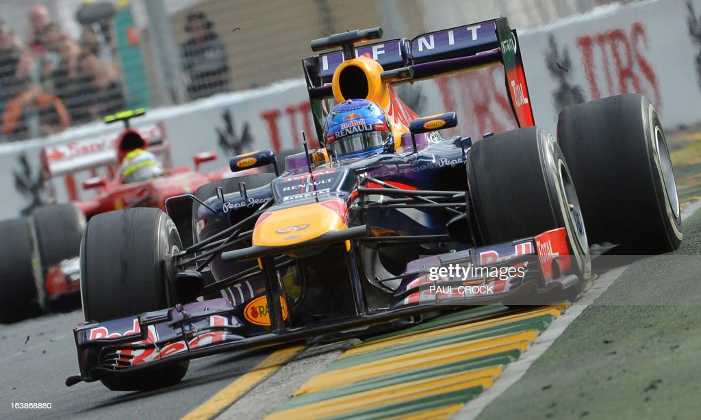 Red Bull driver Sebastian Vettel of Germany powers out of a corner during the Formula One Australian Grand Prix in Melbourne on March 17, 2013. AFP PHOTO / Paul CROCK USE