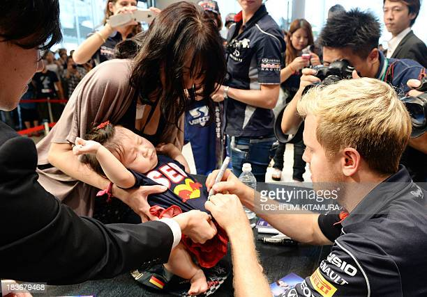 Red Bull driver Sebastian Vettel of Germany signs autographs for fans during a talk show at Nissan Motors headquarters in Yokohama on October 9 2013...