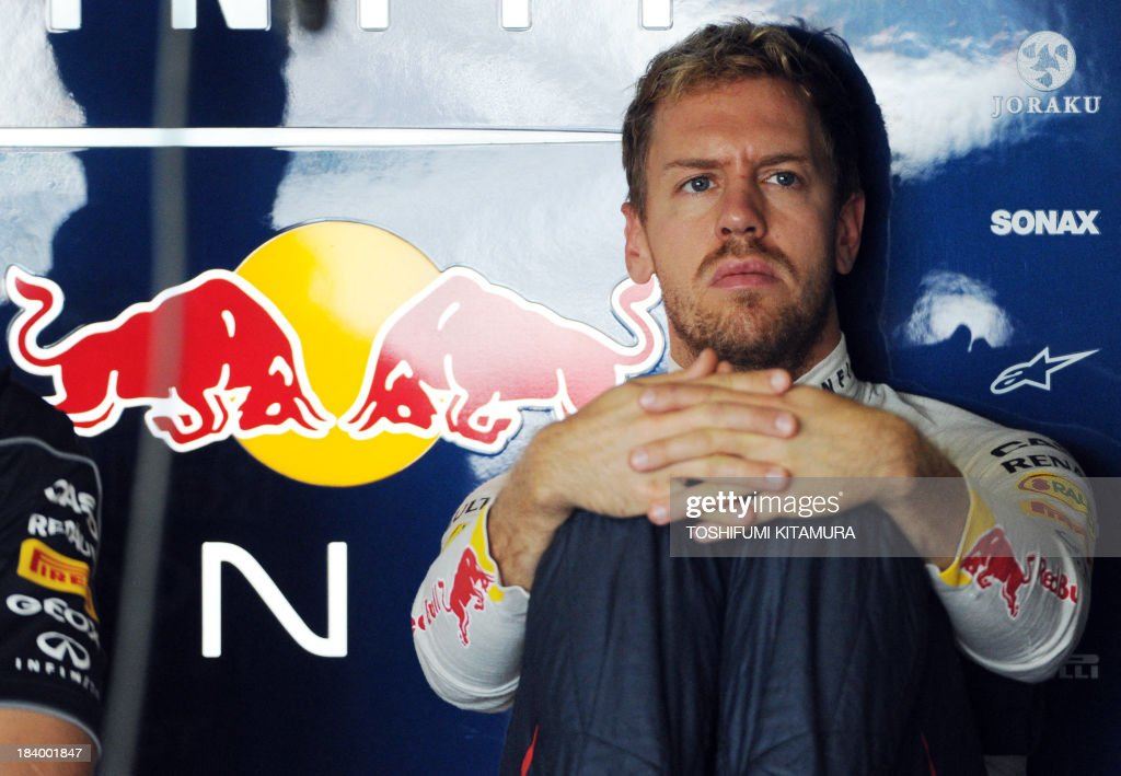 Red Bull driver Sebastian Vettel of Germany watches a TV monitor in his pit during the first free practice session in the Formula One Japanese Grand Prix at the Suzuka circuit on October 11, 2013. Britain's Lewis Hamilton topped the time sheets in the first free practice on October 11 for the Japanese Grand Prix with runaway championship leader Vettel third fastest amid spins, run-offs and a flying wheel.