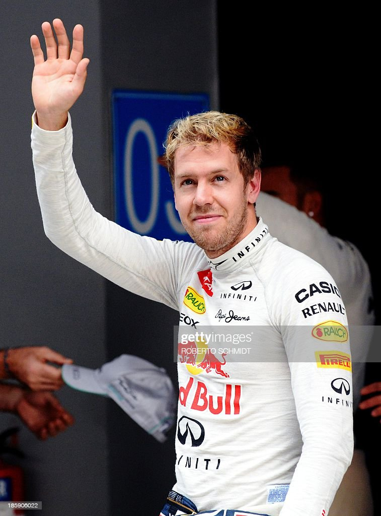 Red Bull driver Sebastian Vettel of Germany waves to the crowd after qualifying first for pole position for the Formula One India Grand Prix at The Buddh International circuit in Greater Noida on the outskirts of New Delhi on October 26, 2013, ahead of the Formula One Indian Grand Prix 2013. The Formula One Indian Grand Prix 2013 takes place on October 27. AFP PHOTO/Roberto SCHMIDT