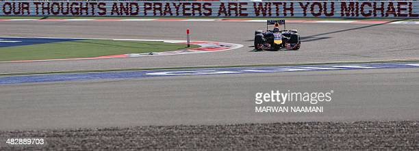 Red Bull German driver Sebastian Vettel steers his car past a banner that reads ' Our thoughts and prayers are with you Micheal' during the third...